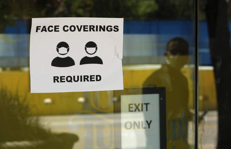 A man wearing mask to protect against the spread of COVID-19 is reflected next to a sign requiring face coverings at a business in San Antonio, Wednesday, June 24, 2020, in San Antonio. Cases of COVID-19 have spiked in Texas and the governor of Texas is encouraging people to wear masks in public and stay home if possible. (AP Photo/Eric Gay)