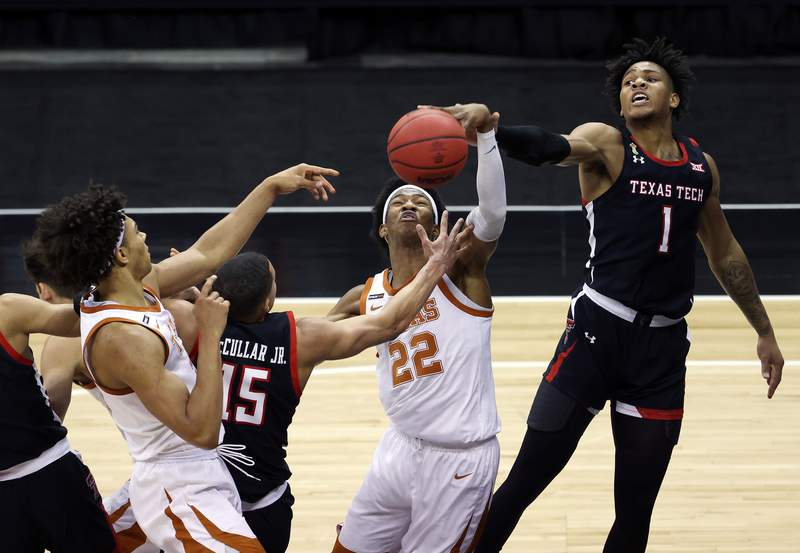 KANSAS CITY, MISSOURI - MARCH 11:  Kai Jones #22 of the Texas Longhorns battles Kevin McCullar #15 and Terrence Shannon Jr. #1 of the Texas Tech Red Raiders for a rebound during the quarterfinal game of the Big 12 basketball tournament at the T-Mobile Center on March 11, 2021 in Kansas City, Missouri. (Photo by Jamie Squire/Getty Images)