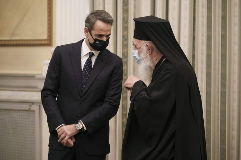 In this photo provided by the Greek Prime Minister's Office, Greece's Prime Minister Kyriakos Mitsotakis, left, talks with Archbishop of Athens and All Greece Ieronimos during a swearing-in ceremony of the new cabinet at the Presidential Palace in Athens, Tuesday, Jan. 5, 2021. Greece's powerful Orthodox Church is rebelling against a government order to briefly close places of worship under a weeklong drive to tighten virus restrictions before the planned reopening of schools. The conservative Church's ruling body issued a statement Monday directing priests to admit worshippers during indoor services for Wednesday's feast of the Epiphany. (Dimitris Papamitsos/Greek Prime Minister's Office via AP)