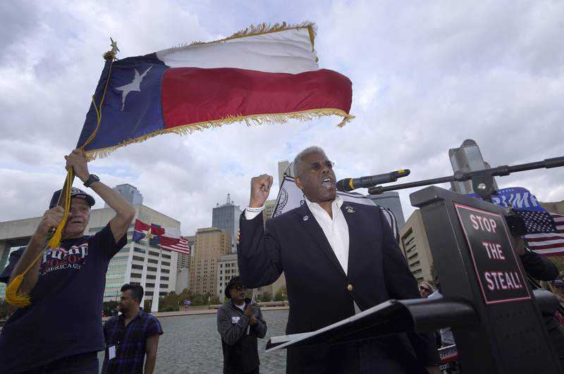 FILE - In this Nov. 14, 2020 file photo, Texas GOP chairman Allen West, right, speaks to supporters of President Donald Trump during a rally in front of City Hall in Dallas. West announced Friday, June 4, 2021, he was stepping down less than a year into a combative tenure of challenging his own party's top leaders, including leading a protest outside Republican Gov. Greg Abbott's mansion. (AP Photo/LM Otero File)