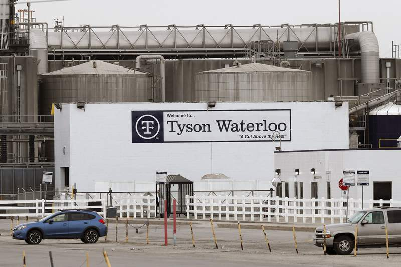 In this May 1, 2020, file photo, vehicles sit in a near empty parking lot outside the Tyson Foods plant in Waterloo, Iowa. A group of worker advocacy organizations has filed a civil rights complaint with the U.S. Department of Agriculture alleging that meat processing companies Tyson and JBS have engaged in workplace racial discrimination during the coronavirus pandemic. The complaint alleges the companies adopted polices that reject U.S. Centers for Disease Control and Prevention guidance on distancing and protective gear on meat processing lines. The complaint says the operating procedures have a discriminatory impact on mostly Black, Latino, and Asian workers. (AP Photo/Charlie Neibergall, file)