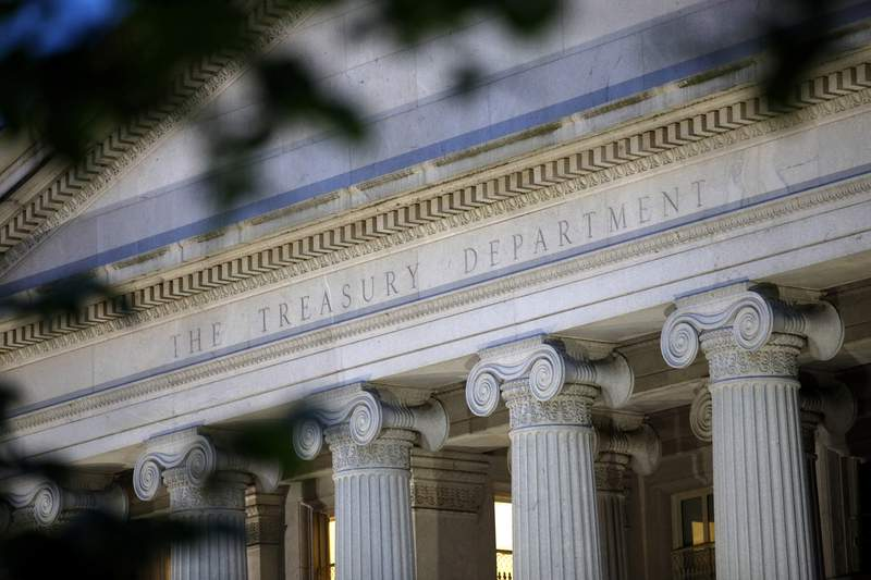 FILIE - This June 6, 2019, file photo shows the U.S. Treasury Department building at dusk in Washington. On Monday, May 3, 2021, the Treasury Department said it expects to borrow $463 billion in the current April-June quarter and $2.28 trillion for the full budget year, as the government finances continued pandemic relief measures. (AP Photo/Patrick Semansky, File)