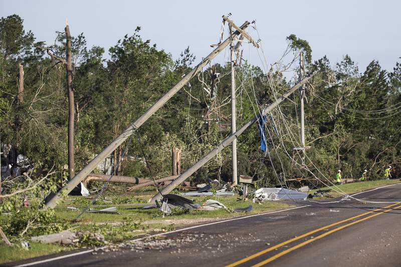Utility poles are knocked off their foundation, dropping power lines, after a tornado ripped a swath of destruction through the area on Thursday, April 23, 2020 in Onalaska, Texas. Maynard was inside his home when the tornado devastated the area. Severe weather is moving through southern Mississippi and Alabama after apparent tornadoes tore through parts of Oklahoma, Texas and Louisiana. Multiple people have been killed, (Brett Coomer/Houston Chronicle via AP)