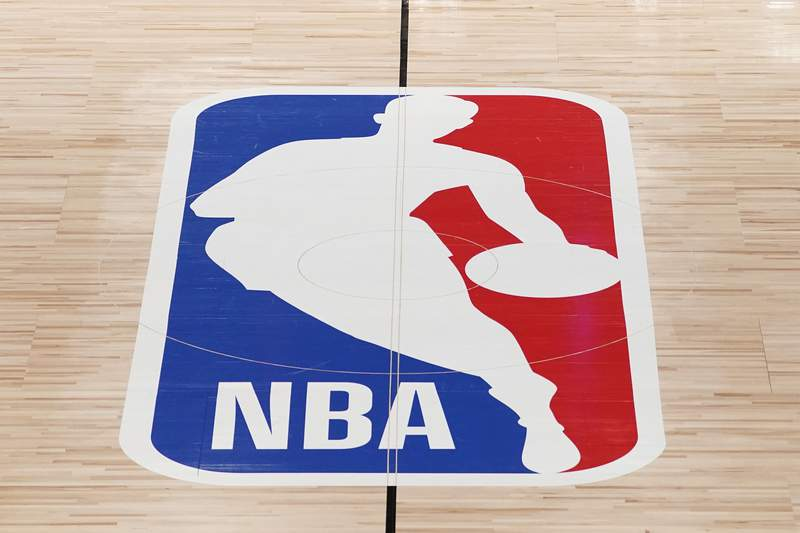 FILE - The NBA logo in shown on a basketball court in Lake Buena Vista, Fla., in this Friday, Aug. 28, 2020, file photo. Pacers coach Rick Carlisle says his new team has a very high vaccination rate but declined to give a specific number because of privacy concerns. He did say Monday during NBA media day that all members of the Indiana coaching staff are fully vaccinated. Carlisle is back in Indiana, where he coached from 2003 through 2007. Training camps open Tuesday and the pandemic will affect a third NBA season and already means some players will be missing on media day.(AP Photo/Ashley Landis, Pool, File)
