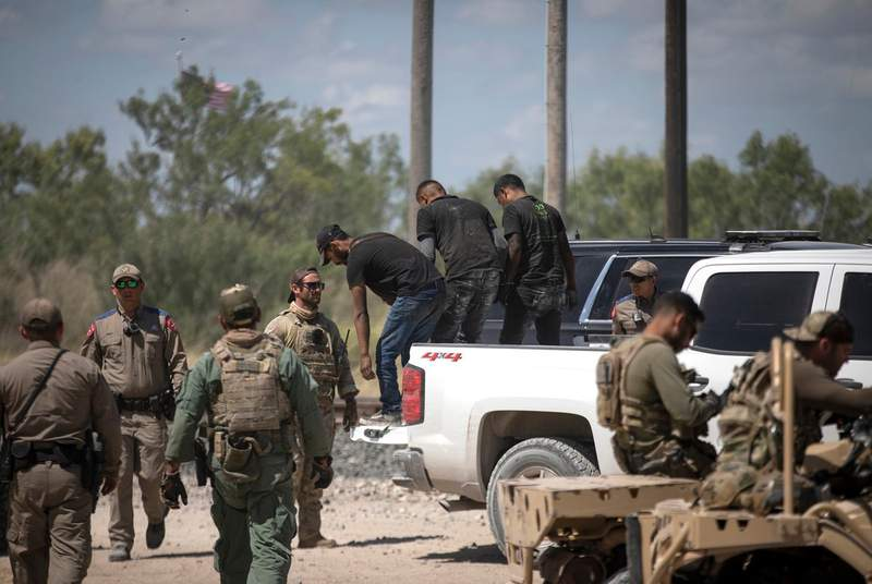 A group of migrants walk off a pick-up truck after being apprehended by Department of Public Safety officers at a train depot in Spofford on Aug. 25, 2021.