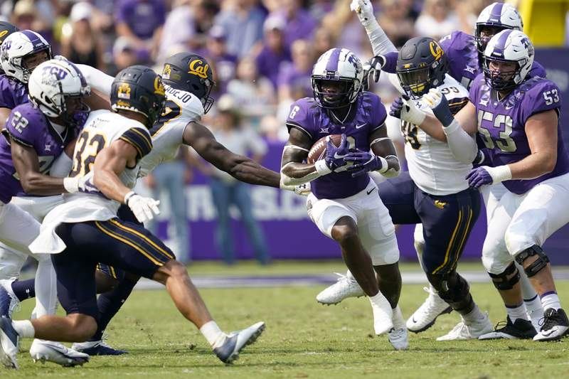 TCU running back Zach Evans (6) finds the gap as he carries the ball past California defensive end Ethan Saunders (99) and others in the first half of an NCAA college football game in Fort Worth, Texas, Saturday, Sept. 11, 2021. (AP Photo/Tony Gutierrez)