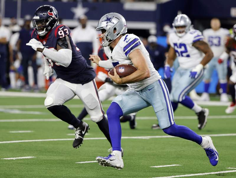 FILE - In this Aug. 21, 2021, file photo, Dallas Cowboys quarterback Ben DiNucci, front right, runs the ball as Houston Texans defensive end Shaq Lawson (93) pursues in the second half of a preseason NFL football game in Arlington, Texas. The New York Jets have acquired edge rusher Lawson from the Texans in exchange for a sixth-round pick in next year's NFL draft, according to a person with direct knowledge of the deal. (AP Photo/Michael Ainsworth, File)