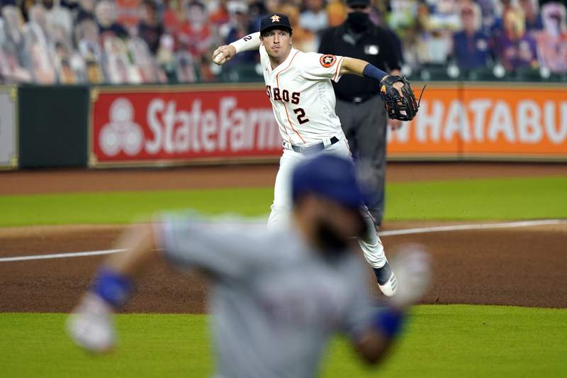 Houston Astros third baseman Alex Bregman (2) throws to first for the out after fielding a ground ball by Texas Rangers' Isiah Kiner-Falefa, bottom, during the fourth inning of a baseball game Wednesday, Sept. 16, 2020, in Houston. (AP Photo/David J. Phillip)