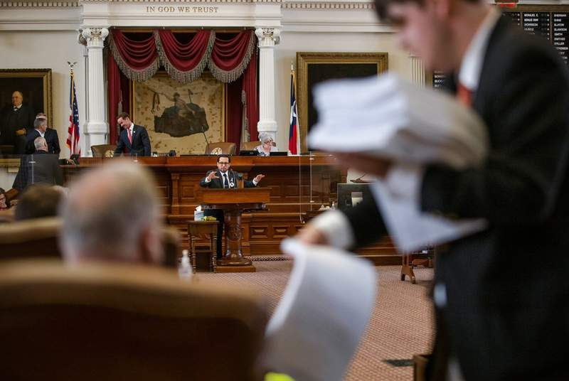 A staffer passes out papers while state Rep. Diego Bernal, D-San Antonio, speaks during session on the House floor at the state capitol on May 25, 2021.